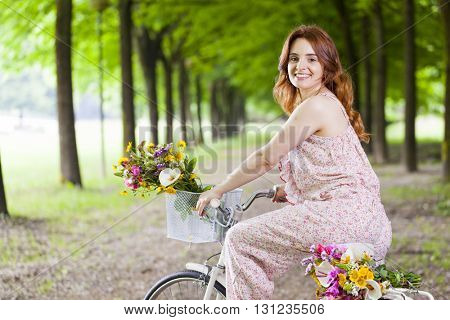 Beautiful young woman riding on bike at the park