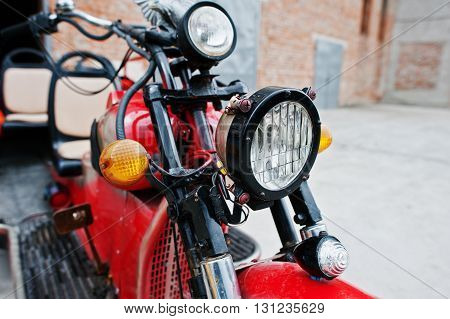 Close up headlight of old red retro motorcycle