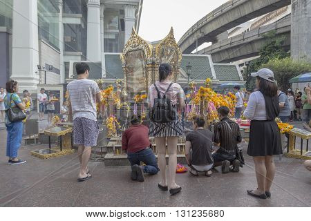 BANGKOK THAILAND - APR 17 : group of tourist pray to Erawan shrine at Ratchaprasong Junction on april 17 2016 Thailand. Erawan shrine is one of famously sacred item in Ratchaprasong area