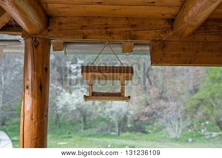 Bird feeder on the porch cottage made of logs of wood