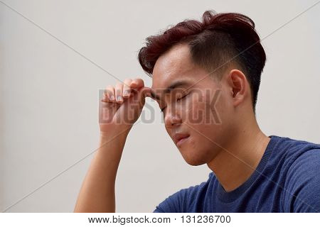 Young asian male looking sad with hands on his head