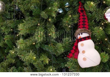 snowman ornament hanging on christmas a tree