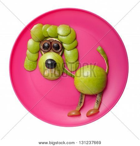 Angry poodle made of apple on pink plate