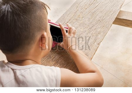 Little Asian boy playing game on mobile or cellphone