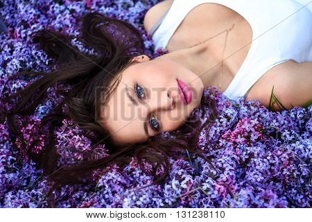 Young beautiful girl lies on the lilac flowers looking at the camera.