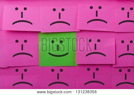 Happy and unhappy concept. Background of sticky notes. Green sticky note is among pink sticky notes.