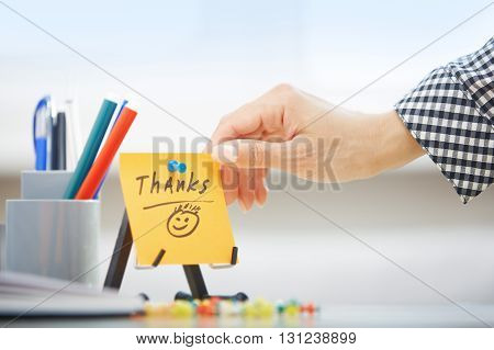 Human hand holding adhesive note with Thanks text
