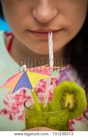 Woman holding and drinking a glass of fresh kiwi smoothie decorated with colorful paper umbrella