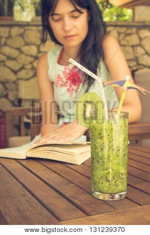 Glass of fresh kiwi smoothie and drinking straw on the desk with girl reading a book in the background.