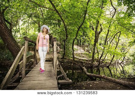 Young youful woman with sunhat posing on wooden bridge in the forest. Beauty and nature. Positive emotions. Brunette woman. Show off. Outdoors scene.
