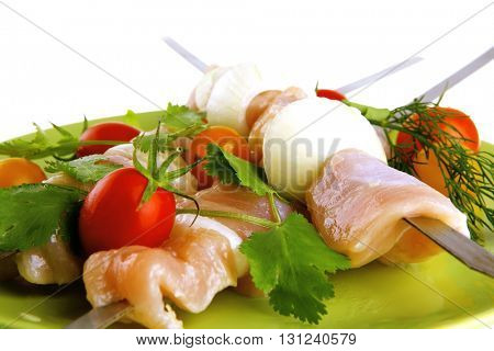 raw uncooked chicken shish kebabs with tomatoes on metal steel skewers on green plate isolated over white background