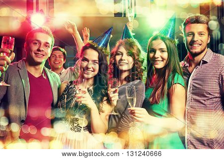 party, holidays, celebration, nightlife and people concept - smiling friends in party caps with glasses of champagne in club
