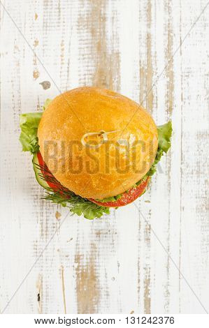 Big beef steak burger with vegetables and herbs on rustic wooden background top view