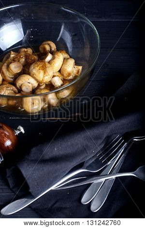Roasted marinade mushrooms in bowl on dark background with salt and paper near it.