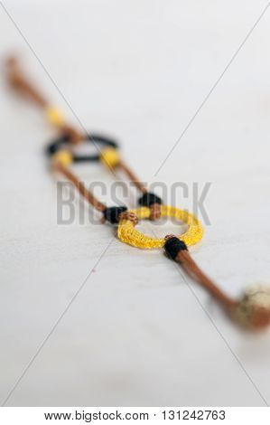 Crochet bracelet with black, yellow and brown on a white background