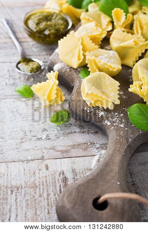 Homemade raw Italian saccottini filled with green pesto on wooden vintage cutting board with basil leaves. Selective focus. With copy space.