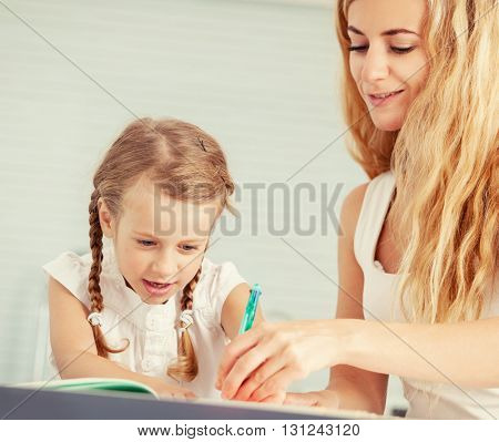 Parent teaches a child to write. Mom helping her daughter do homework