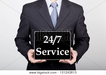 technology, internet and networking in business concept - businessman holding a tablet pc with 24 7 service sign. Internet technologies in business.