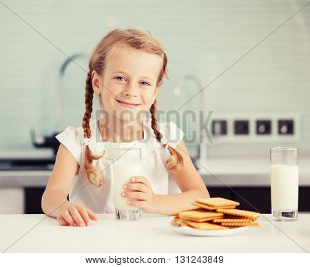 Child drinking milk at home. Happy little girl eating at home