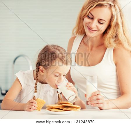Child with mother drinking milk. Happy family eating at home