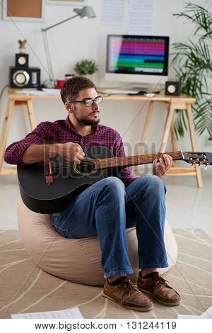 Inspired young musician playing guitar in his home studio