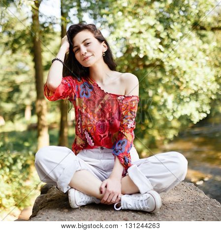 The girl sitting in bright clothes with elegant dark long hair and open emotion in the summer park