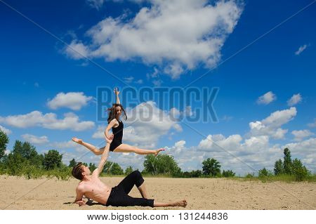 Contemporary dance. Man and woman in passionate dance pose on beach. Young couple dancing modern dance in beautiful pose outdoors. Girl in jump against the sky, clouds. A man with naked torso on sand.