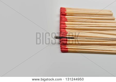Many Red Head Matches And One Burned Put Straight In Line On White Background