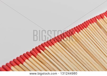 Many Red Head Matches Placed Straight In Line On White Background. Room For Text
