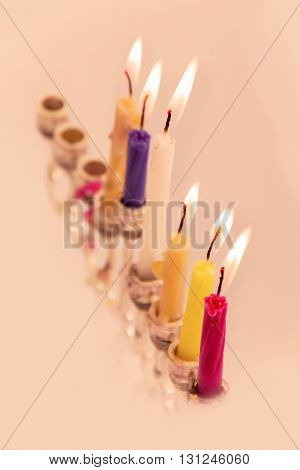 Hanukah candle with glowing colorful candles next to the yellow dreidel