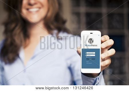 Malaga, Spain - June 30, 2016: Wordpress mobile app in a phone screen. Woman holding it in the hand and showing it to the screen. Wordpress is a popular CMS to create web sites.