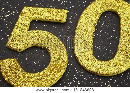 Number fifty golden color over a black background. Anniversary. Horizontal