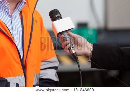 Press interview. Journalist holding a microphone conducting an TV or radio interview.