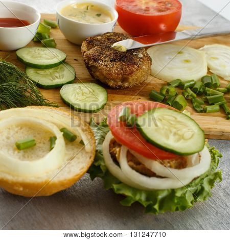 Cooking process of a sandwich burger ingredients on wooden cutting board on wooden table against white background fresh vegetables herbs fried meat buns sauces and knife close up shallow DOF