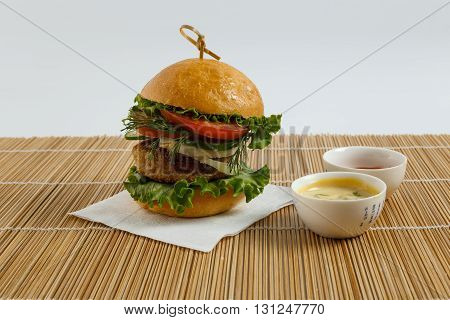 Big beef steak burger with vegetables and herbs on white plate and sauces on bamboo placemat against white background horizontal view close up