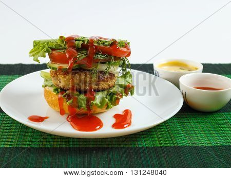 Big beef steak burger with vegetables and herbs on white plate and sauces on green bamboo placemat against white background horizontal view close up