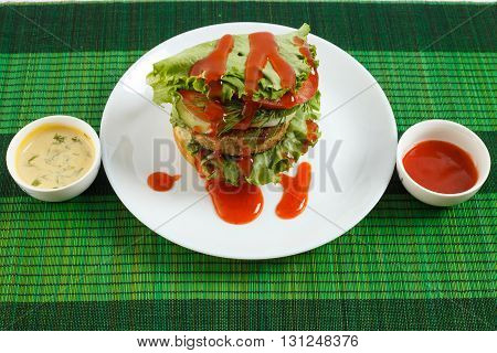 Big beef steak burger with vegetables and herbs and sauces on green bamboo placemat horizontal view