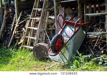 wheelbarrow leaning overhead on a shed with messy stacked wood in a country garden