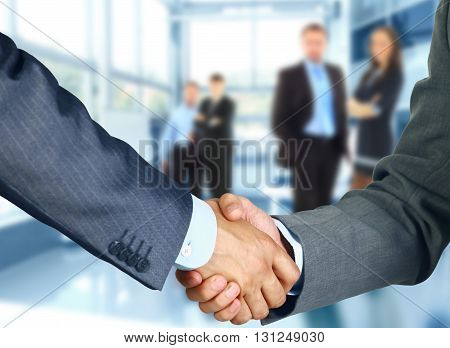 Business associates shaking hands in modern office