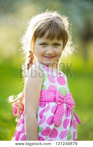 Little happy girl in colored summer dress