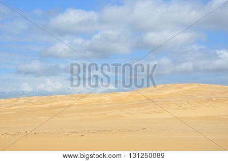 Remote, deserted sand dune under blue sky