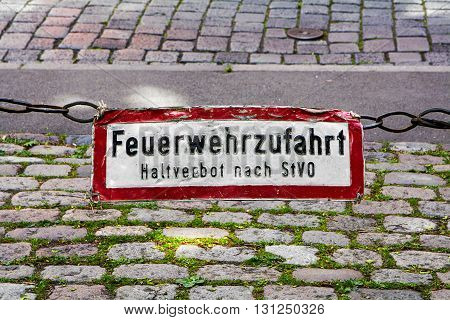 Old sign labeled with the German words Feuerwehrzufahrt Haltverbot nach StVO (fire rescue path halt banned by highway code) hanging above a street with cobblestones