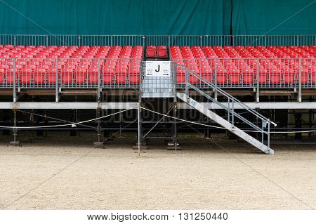 Temporary raked red spectator seating for outdoor event