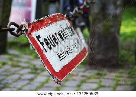 Old sign labeled with the German words Feuerwehrzufahrt Haltverbot (fire rescue path halt banned ) hanging above a street with cobblestones view from the side selected focus narrow depth of field