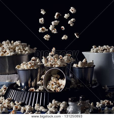 Home made popcorn in alluminium glasses with popcorn in motion on dark background, dark rustic still life. Square image