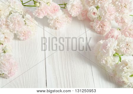 frame from small Roses on wooden background.