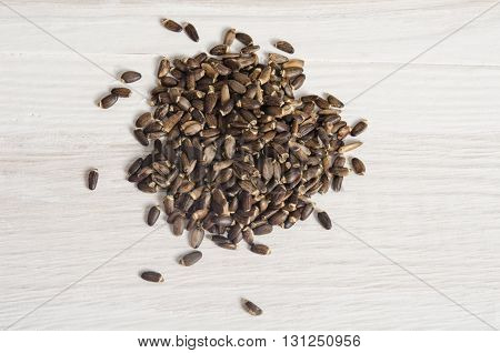 Seeds of a milk thistle (Silybum marianum Scotch Thistle Marian thistle ) on wooden table
