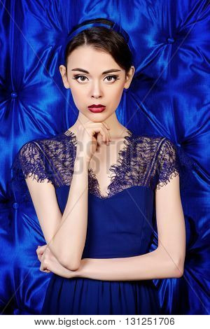 Portrait of a pretty young woman wearing blue lace dress and a blue bow on hair. Pin-up style. Beauty, cosmetics.