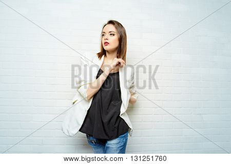 Modern young woman in casual jeans and jacket posing by a white brick wall. Beauty, fashion. Youth style.