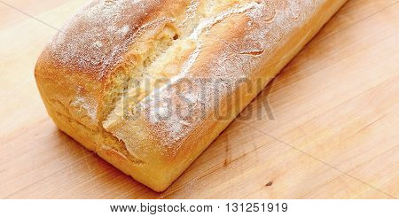 Fresh baked bread loaf on wooden plate. Fresh bread. Baked bread.